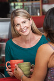Smiling Blond Woman with Friend in Bistro
