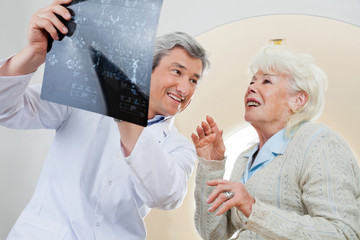 Doctor With Patient Looking At X-ray