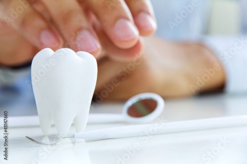 Poster dentist holding molar,dental concept
