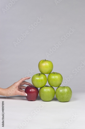 Hand selecting an apple from a stack