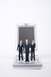 Businessman figurines standing on mobile keypad