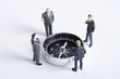 Businessman figurines standing and looking at compass