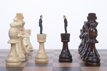 Businessman figurines standing on chess piece