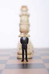 Businessman figurine standing in front of chess pieces