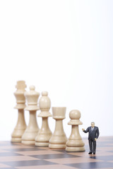 Businessman figurine standing next to chess pieces