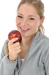 Junge Frau in Freizeitanzug isst Apfel