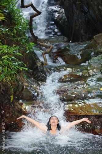 Woman in wild waterfall