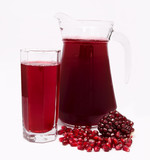 Pomegranate juice in pitcher and pomegranates isolated on white