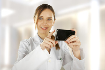 Portrait of a young smiling doctor using smartphone