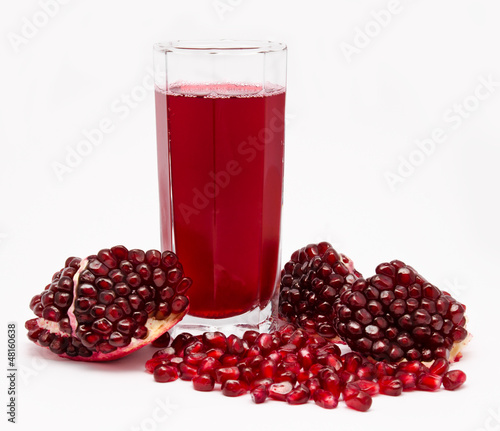 Pomegranate juice in glass and pomegranates isolated on white
