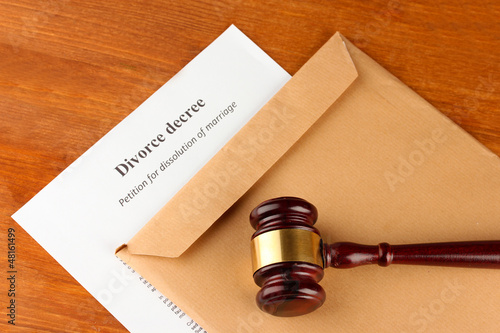 Divorce decree and envelope on wooden background