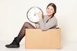 junges Mädchen mit Uhr sitzt in einem Karton
