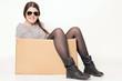 junges Mädchen sitzt lässig in einem Karton