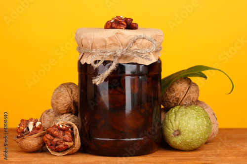 jam-jar of walnuts on wooden table on orange background