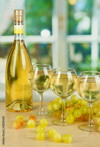 White wine in glass with bottle on window background
