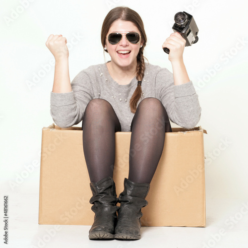 glückliches junges Mädchen sitzt im Karton