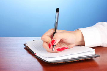 Hand signing in notebook  on wooden table on color background