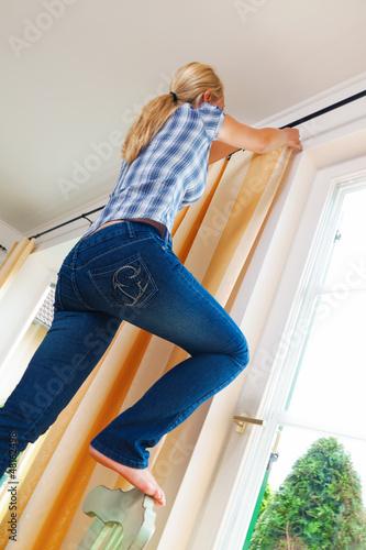 Hausfrau mit Gardinen.