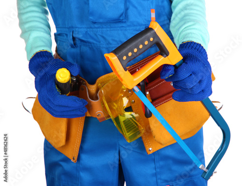 Male builder in blue overalls with saw isolated on white
