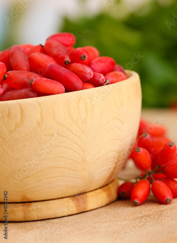 ripe barberries in wooden bowl with green leaves, on table