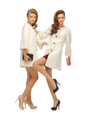 two teenage girls in white coats with clutches