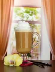 Fragrant coffee latte in glass cup with vanilla pods,