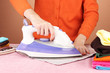 Young woman ironing her clothes, on brown background