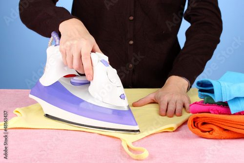 Young woman ironing her clothes, on blue background