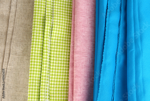 Pile of different fabrics close-up background