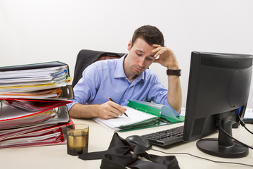 Stressed businessman filling paper documents at work