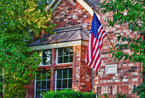 American flag hanging on the front of the house