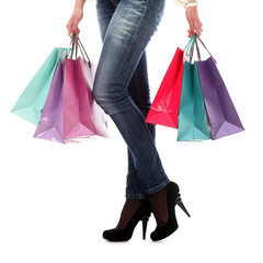 Shopping bags near legs in jeans and high heels