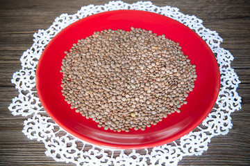 Lentils in the red plate on wood background