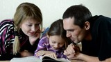 father, mother and daughter reading a book