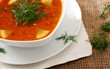 Image of bowl of hot red soup on brown tablecloth