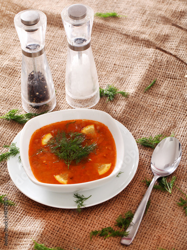 Soup served with the salt, pepper and spoon