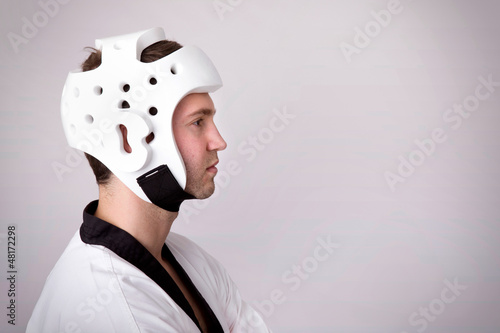 Young man with martial arts helmet standing on grey background