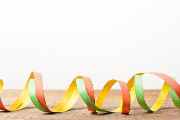 Holzbrett mit bunten Luftschlangen
