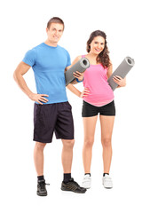 Two young athletes holding exercising mats