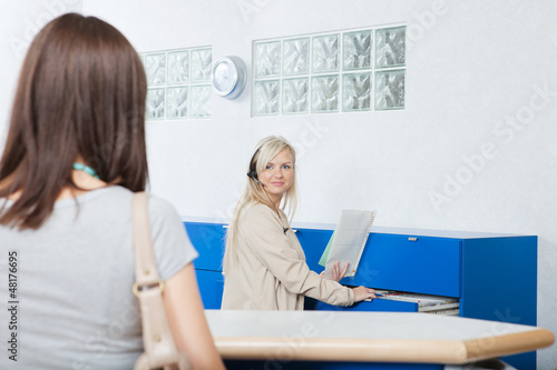 Receptionist Looks At Woman In Dentist's Office