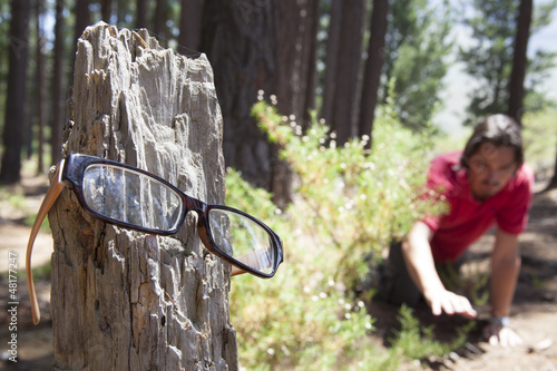 man looking for his spectacles in the woods