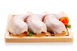 Raw chicken legs on cutting board on white background