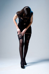 A girl in a dress on a gray background straightens stockings