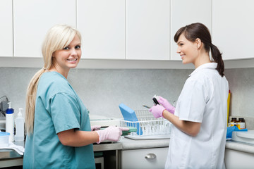 Smiling Dentist With Assistant Cleaning Medical Instruments At C