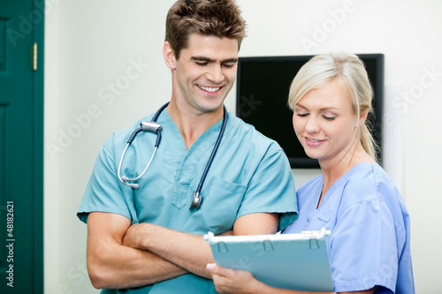 Young Female Nurse Showing Clipboard To Male Vet