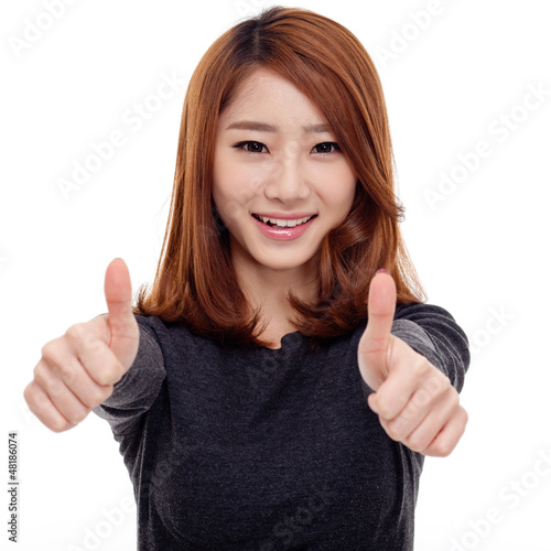 Young Asian woman showing thumb isolated on white background.