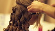 Hairdresser curls hair of model on fashion show