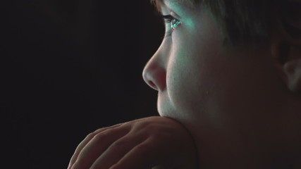 Young boy watching cartoons in a dark room