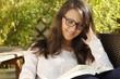 Hübsche Frau mit Brille liest ein Buch auf der Terrasse