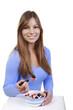 Glückliche Frau ißt Müsli mit Früchten